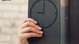 Imagem do post: 3 dicas que irão dar mais produtividade ao seu dia. Na imagem pode ser visto uma mão segurando um livro, com o desenho de um relógio representando a produtividade